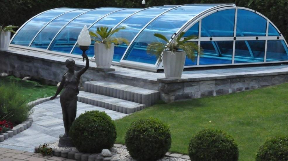 Cranpool Cabriodom ist eine Ganzjahresabdeckung. Das Bild zeigt ein Schwimmbecken Ozean von Cranpool mit einem geschlossenen Cabriodom. Das Schwimmbecken wurde auf eine Steinmauer aufgebaut. Vor dem Schwimmbecken sind einige Grünpflanzen und eine Statue aus Stein zu sehen. Zum Schwimmbecken führt eine Steintreppe.