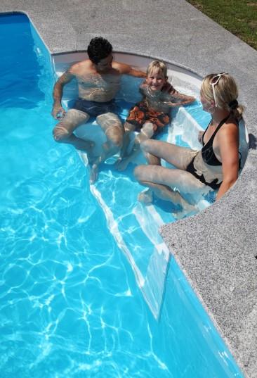 Heimwerker-Schwimmbecken Cranthermo ist ein Rechteckpool für Heimwerker. Das Bild zeigt einen Mann eine Frau und ein Kind auf der Einstiegstreppe sitzend.