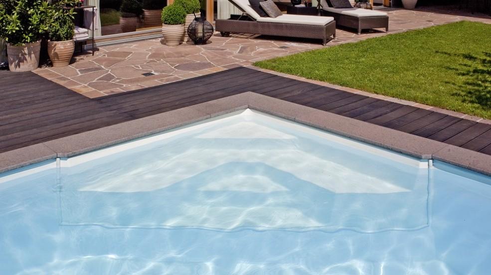 Cranpool Einstiegshilfen dienen den sicheren Einstieg ins Schwimmbecken. Das Bild zeigt eine Cranpool Ecktreppe in einem Ozean Pool integriert. Am Beckenrand wurde dunkles Holz und braune Pflastersteine verlegt. Im Hintergrund stehen zwei Liegestühle und ein paar Grünpflanzen.