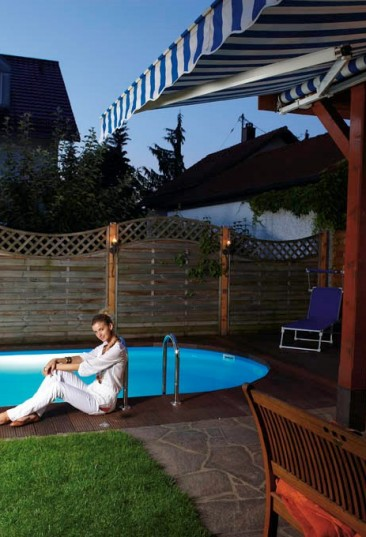 Einbau-Schwimmbecken Miami bietet ein auf die Haus-und Gartenarchitektur abgestimmtes Schwimmparadies. Auf dem Bild sieht man ein ovales kleines Schwimmbecken Miami. Der Beckenrand ist mit Lärchenbrettern verbaut. Auf dem Beckenrand sitzt eine Frau in weißer Bekleidung. Auf der Terrasse vor dem Schwimmbecken stehen ein Tisch und eine Bank. Der Sichtschutz im Hintergrund ist durch Holzelemente gegeben.