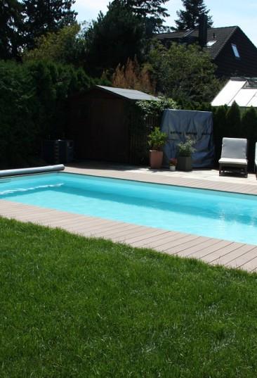 Rechteck-Schwimmbecken Ozean ist das High-Class-Schwimmbecken made in Austria. Das Bild zeigt ein Schwimmbecken Ozean das von hellen Holzbrettern umgeben ist. Im Hintergrund sind Häuser zu sehen. Der Sichtschutz ist durch eine Hecke gegeben. Am Beckenrand sind zwei Liegestühle mit weißer Auflage aufgestellt.