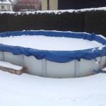 Cranpool PE-Winterabdeckplane schützt Ihr Schwimmbecken in der kalten Jahreszeit. Das Bild zeigt ein ovales Schwimmbecken Sun Remo mit einer blauen Winterabdeckung. Im Hintergrund ist eine Hecke und Häuser zu sehen. Das Becken ist von Schnee bedeckt und umgeben.