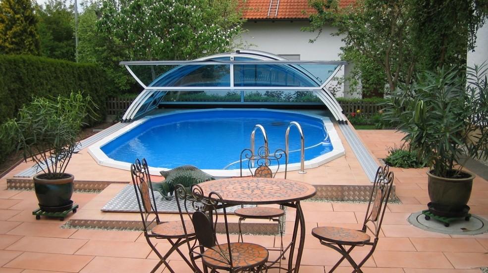 Stahlwand-Swimmingpool Royal wird in Österreich hergestellt. Das Bild zeigt ein Stahlwand Schwimmbecken Royal mit geöffneten Cabriodom. Rund um das Becken sind roto Steine verlegt. Im Hintergrund ist ein Familienhaus. Davor sind einige Bäume zu sehen. Vor dem Schwimmbecken steht ein Tisch mit vier Stühlen. Links und rechts vom Becken stehen Grünpflanzen.