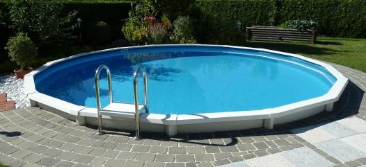 Cranpool Royal besticht durch eine rasche Bauzeit. Das Bild zeigt ein rundes Schwimmbecken Royal das von grauen Pflastersteinen umrandet wird. Hinter dem Schwimmbecken ist ein Blumenbeet und ein Hochbeet angelegt. Den Sichtschutz hinter dem Schwimmbecken bildet eine Hecke.