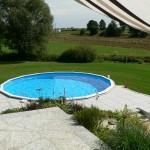 Cranpool Royal besticht durch seine stabile Konstruktion. Das Bild zeigt ein rundes Schwimmbecken Royal das komplett in die Erde eingebaut ist. Im Vordergrund des Beckens wurden graue Steinplatten verlegt. Im Hintergrund ist eine Wiese mit anschließenden Acken.