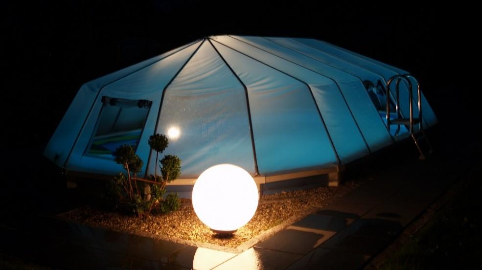 Cranpool Sonnendom schützt Ihr Wasser vor Verschmutzungen. Das Bild zeigt einen geschlossenen Sonnendom in der Nacht. Im Vordergrund ist eine runde Beleuchtung eingeschaltet die das Schwimmbecken ausleuchtet.