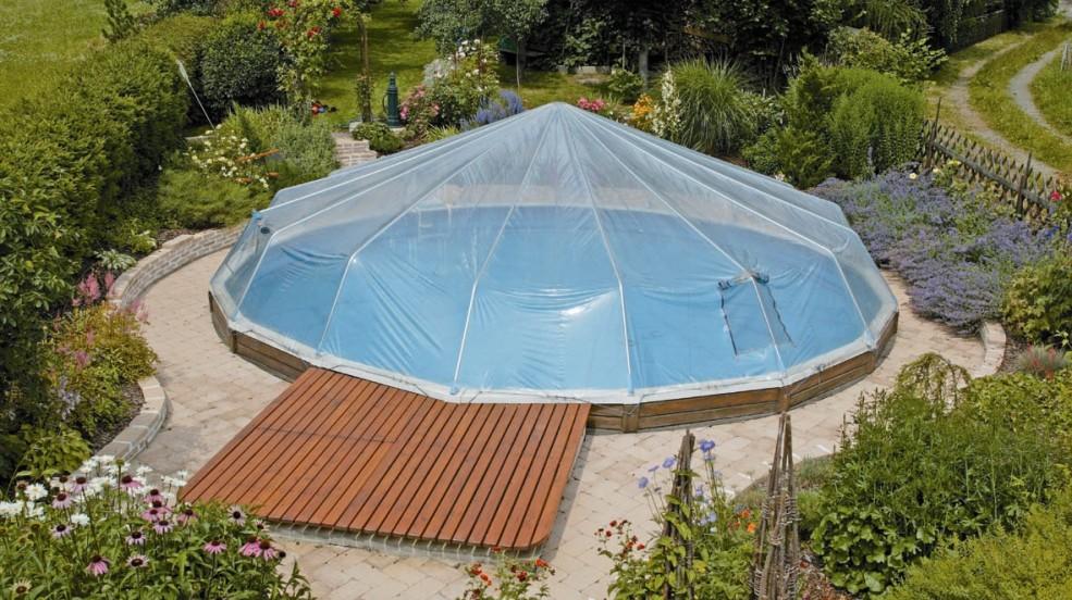 Cranpool Sonnendom sorgt für höhere Wassertemperaturen. Das Bild zeigt ein rundes Schwimmbecken Royal mit einem Sonnendom. Das Schwimmbecken befindet sich in einem schön angelegten Garten mit vielen verschiedenen Blumen und Sträuchern.
