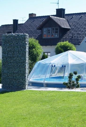 Cranpool Sonnendom sorgt für höhere Wassertemperaturen. Das Bild zeigt einen geschlossenen Sonnendom. Im Hintergrund befindet sich ein Einfamilienhaus. Das Schwimmbecken ist in die Erde eingebaut und von hellen Steinen umgeben. Am linken Beckenrand stehen zwei Steinsäulen.