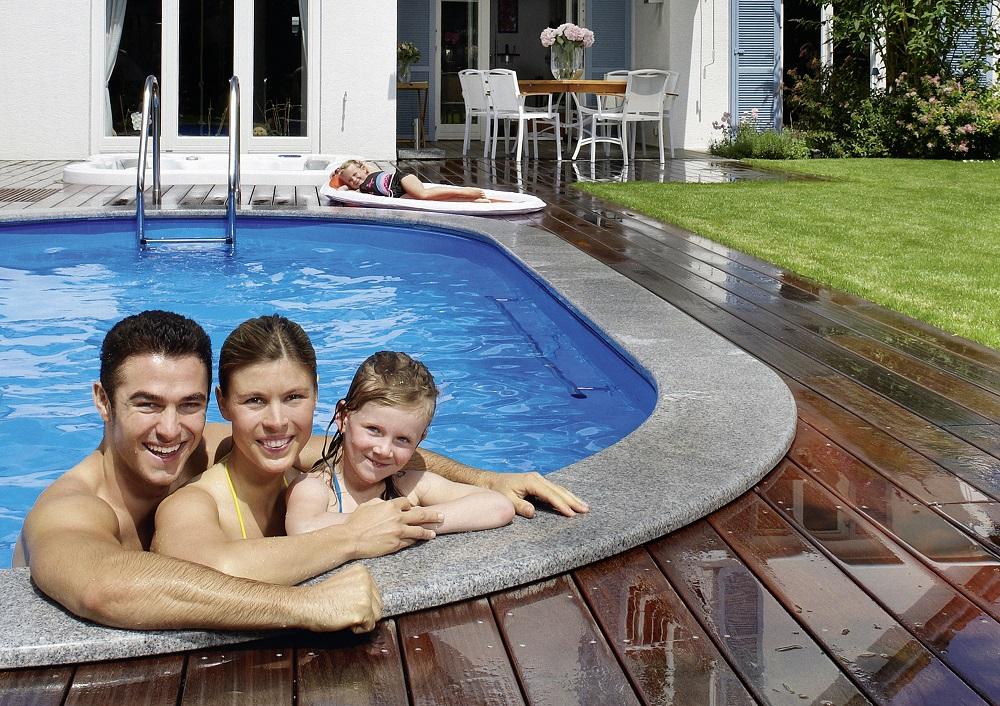Einbau-Schwimmbecken Miami überzeugt durch viele Gestaltungsmöglichkeiten. Das Bild zeigt ein Schwimmbecken Miami mit Granitrand. Rund um das Becken sind Lärchenbretter verlegt. Am vorderen Poolrand ist ein Mann eine Frau und ein kleines Mädchen an den Beckenrand angelehnt. Im Hintergrund ist ein Einfamilienhaus. Vor dem Haus steht ein Tisch mit weißen Sesseln. Davor liegt ein kleines Mädchen.