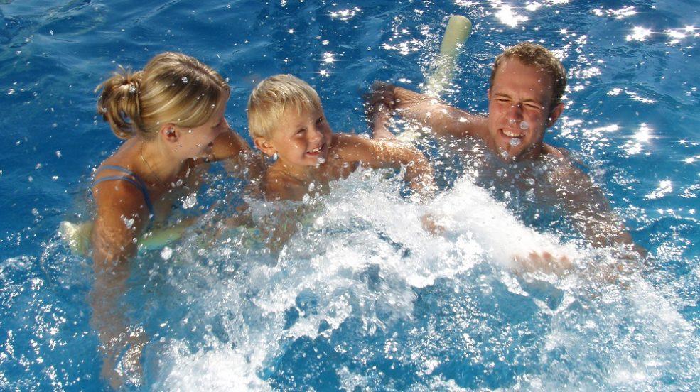 Cranpool Stratos ist ein Aufstellbecken das durch eine einfache Bauweise überzeugt. Das Bild zeigt einen Mann eine Frau und ein Kind beim plantschen im Schwimmbecken. Beim betrachten des Bildes verspürt man badelust.