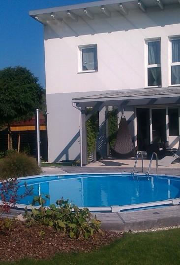Cranpool Sun Remo überzeugt über 10000 zufriedene Kunden bei Cranpool. Auf dem Bild sieht man ein rundes versenktes Schwimmbecken Sun Remo in einem schönen Garten. Der Poolrand ist mit Holzbalken umrandet. Im Hintergrund steht ein Einfamilienhaus.