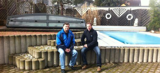 Cranpool Standort Kraubath. Das Bild zeigt zwei Mitarbeiter der Firma Cranpool vor einem Schwimmbecken sitzend. Im Hiintergrund sieht man ein Schwimmbecken Ozean.