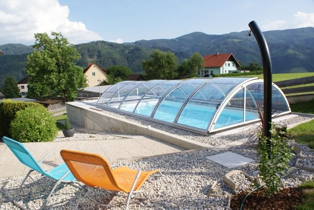 Cranpool Cranthermo mit geschlossenem Cabriodom Klassik. Im Vordergrung ist eine Solardusche aufgebaut. Zwei Liegestühle laden zu erholsamen Stunden am Schwimmbecken ein.