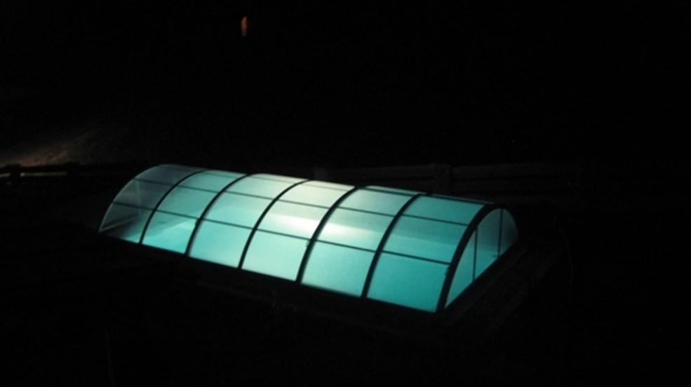Cranpool Cranthermo mit geschlossenem Cabriodom Klassik bei Nacht. Im Schwimmbecken wurden Scheinwerfer eingebaut, ob das Schwimmbecken in der Nacht optimal zu beleuchten.