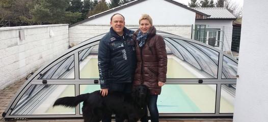 Cranpool Partner Konrfehl ist ihr Partner für das mittlere und nördliche Burgenland. Das Bild zeigt einen Mann und eine Frau mit einem schwarzen Hund. Sie stehen vor einem Schwimmbecken Ozean das mit einem Cabriodom abgedeckt ist. Im Hintergrund sieht man ein Haus. Der Sichtschutz zum Becken wird durch eine Steinmauer gebildet.