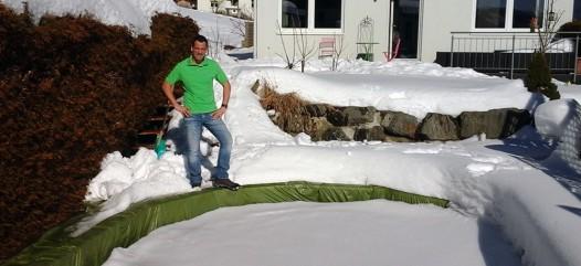 Cranpool Partner Vorarlberg. Das Bild zeigt einen winterlich verschneiten Garten. Das Schwimmbecken ist mit einer grünen Winterabdeckung versehen. Am Beckenrand steht ein Cranpool Partner. Im Hintergrund ist eine Steinmauer und ein Einfamilienhaus.