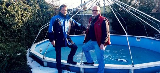 Cranpool Royal überzeugt durch seine rasche Bauzeit. Das Bild zeigt ein Schwimmbecken Royal mit abgebauten Sonnendom. Am vorderen Beckenrand stehen zwei Männer der Firma Cranpool. Im Hintergrund sind einige Bäume zu sehen.