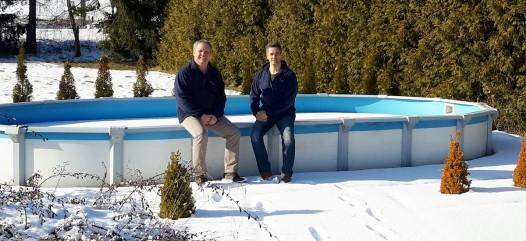 Cranpool Sun Remo überzeugt durch seine hohe Qualität. Das Bild zeigt zwei Verkäufer sitzend auf den vorderen Beckenrand eines Cranpool Sun Remo. Die Umgebung zeigt eine winterliche Landschaft. Im Hintergrund ist eine Hecke zu sehen.