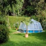 Stahlwand-Swimmingpool Royal von Cranpool, ein ovales Becken mit Sonnendom. Es wurde teilversenkt ins Erdreich.