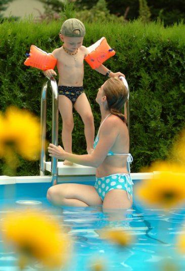 Das Stahlwand-Schwimmbecken Riva, ideal für den kleinen Garten und für Badespass für die ganze Familie. Auf diesem Bild spürt man die gute Stimmung zwischen Mutter und Kind vor dem geplanten Badevergnügen.