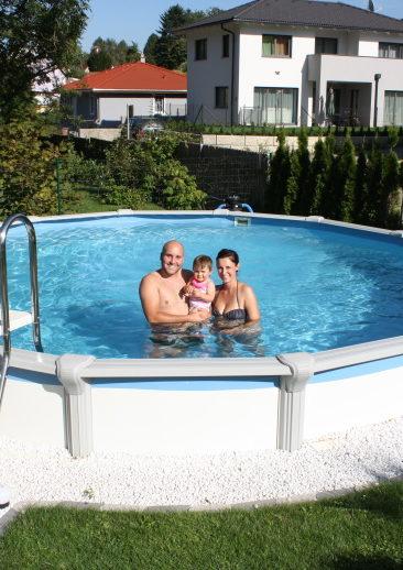 eine jung Familie in einem Cranpool Rundbecken Das Becken ist gut gepflegt das becken steht in einem Garten und hat eine Umrandung aus Kieselsteinen