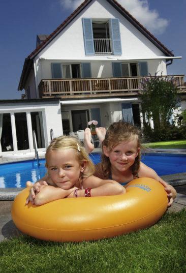 Einbau-Schwimmbecken Miami überzeugt durch viele Gestaltungsmöglichkeiten. Das Bild zeigt ein Schwimmbecken Miami mit Granitrand. Rund um das Becken sind Lärchenbretter verlegt. Am vorderen Poolrand liegen zwei kleine Mädchen, angelehnt an einem gelben Schwimmreifen.. Im Hintergrund ist ein Einfamilienhaus.
