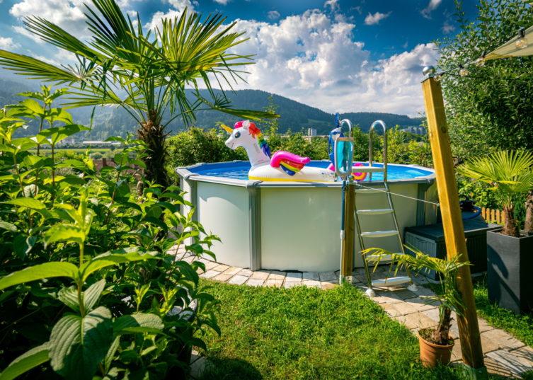Aufstellbecken von Cranpool, in einem kleinen Garten mit palmen und vielen anderen Pflanzen. In dem kleinen Pool schimmt ein aufgeblasenes Wasserspielzeug