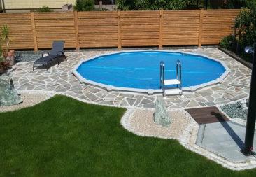 ein rundes Schwimmbecken eingegraben, mit einer Outdoordusche von Cranpool. Das Schwimmbecken ist von einem Steinweg umgeben und ,man erkennt eine Liege und einige Pflanzen im Hintergrund