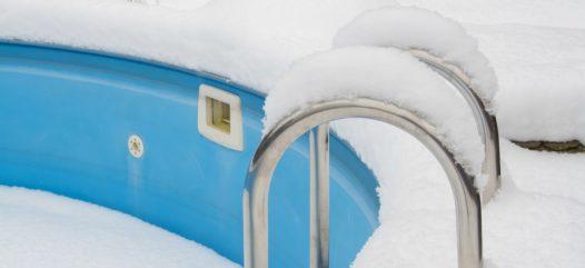 ein schwimmbecken im Winter, welches dem Frost und den Niederschlägen ohne den Schutz einer Winterabdeckplane ausgesetzt ist