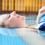 junge Frau im Pool, halb im Wasser, liegt auf einer Wassernudel im Schwimmbecken und genießt ihre Zeit im swimming pool