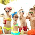 eine Gruppe Kinder, weöche in Badeanzüge, Bikinis und Badehosen einen Tag am Pool genießen, im MOment maxchen sie gerade eine Trinkpasue, alle Kinder haben Sonnenbrillen auf