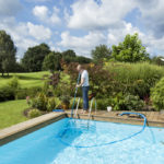 ein stolzer Poolbesitzer bei der Reinigung seines Cranpool Schwimmbeckesn mit einem manuellen Bodensauger